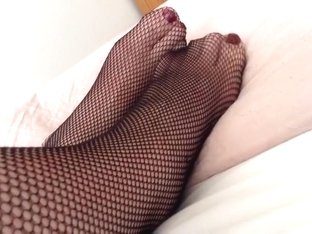 Feet And Legs In Black Fishnet Tights